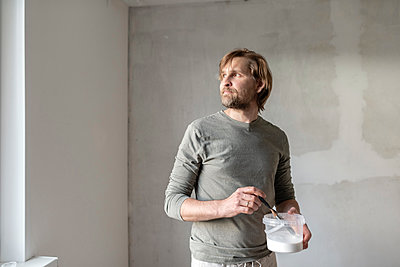 Thoughtful man holding paint can at home - p300m2198169 by Ekaterina Yakunina
