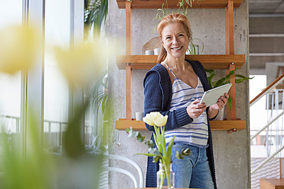 Happy woman with digital tablet standing by rack at home - p300m2265235 by Jo Kirchherr