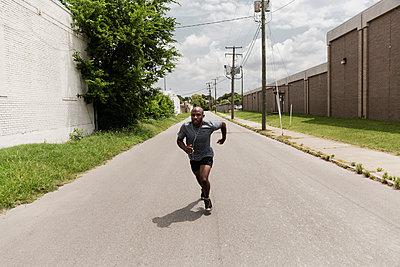 Black man running on city street - p555m1420909 by Roberto Westbrook