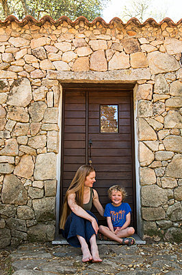Mother and son sit in front of stone house - p628m1476239 by Franco Cozzo