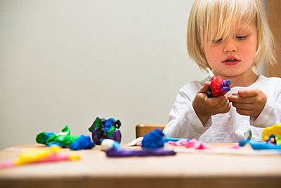 Three year old boy playing with modeling clay - p924m937065f by JLPH