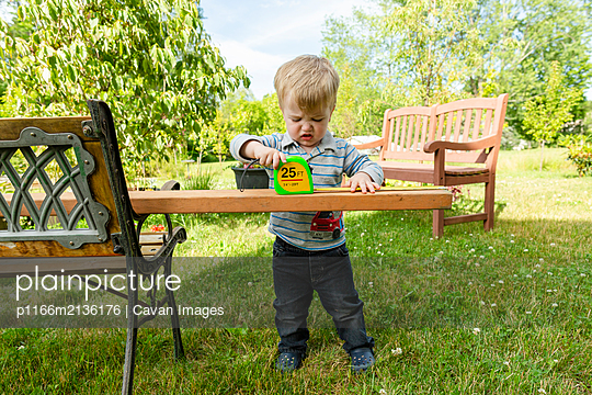 Toddler boy looks frustrated while measuring wooden board outdoors - p1166m2136176 by Cavan Images