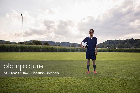 Junge mit Ball auf dem Fußballplatz - p1206m1170047 von Christian Brecheis