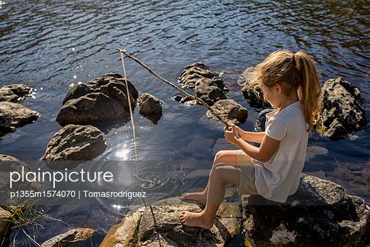 Mädchen angelt am Seeufer - p1355m1574070 von Tomasrodriguez
