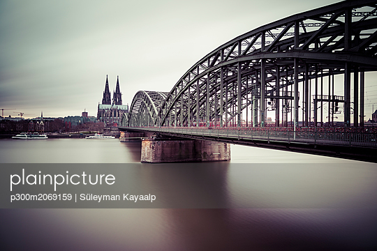 Germany, Cologne, view to Cologne Cathedral with Hohenzollern Bridge and Rhine River in the foreground - p300m2069159 by Süleyman Kayaalp