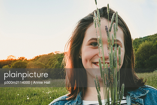 Portrait of smiling teenage girl with grasses at sunset - p300m2114000 von Annie Hall