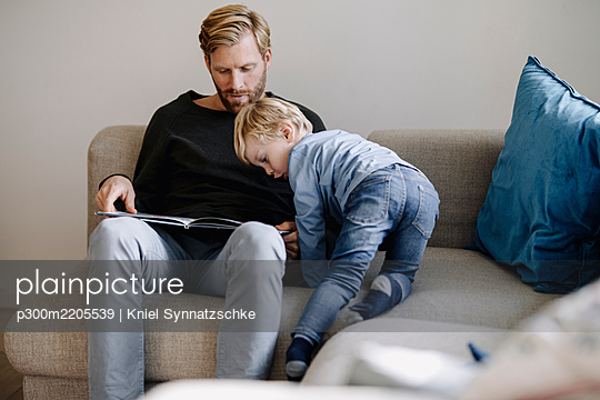 Father and son looking at book on couch at home - p300m2205539 by Kniel Synnatzschke