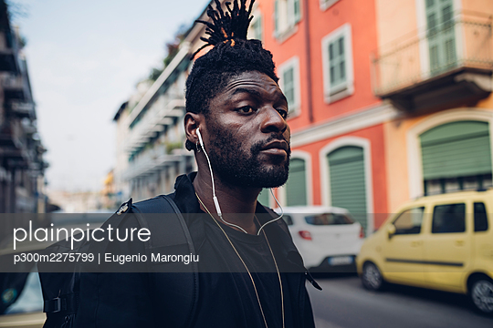 Man with backpack listening music through in-ear headphones - p300m2275799 by Eugenio Marongiu