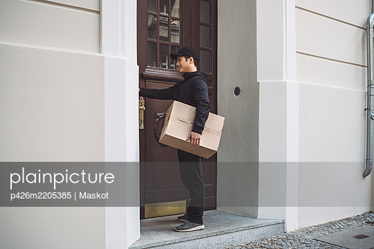 Full length of delivery man with package standing at doorstep - p426m2205385 by Maskot