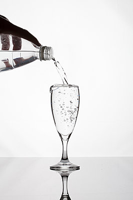 Hand pouring water from bottle into glass - p1687m2284327 by Katja Kircher