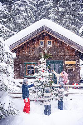 Austria, Altenmarkt-Zauchensee, family decorating Christmas tree at wooden house - p300m2042021 by Hans Huber