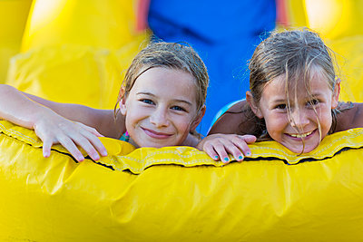 Caucasian girls playing together on inflatable castle - p555m1421236 by Marc Romanelli