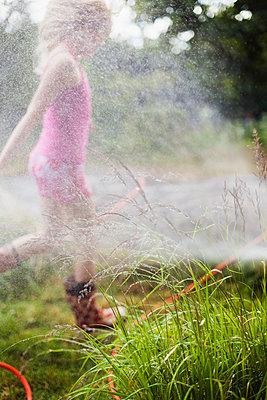 Girl Running Into The Water Sprinklers In The Garden - p847m888798 by Bildhuset