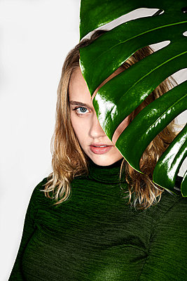 Young woman behind foliage plant - p890m2231070 by Mielek