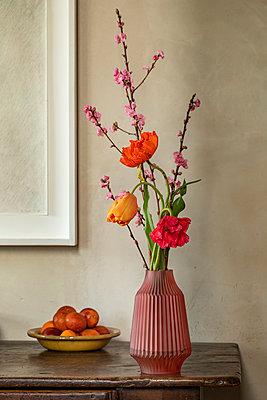 Rote Vase mit Tulpe, Pfirsichzweig und Mohn vor einem Bild auf einem Holztisch. - p948m2134097 von Sibylle Pietrek