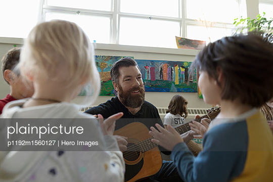 plainpicture - plainpicture p1192m1560127 - Male teacher with guitar te... - plainpicture/Hero Images