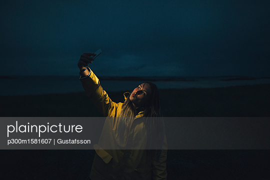 France, Brittany, Landeda, Dunes de Sainte-Marguerite, woman taking a selfie on the beach at night - p300m1581607 von Gustafsson