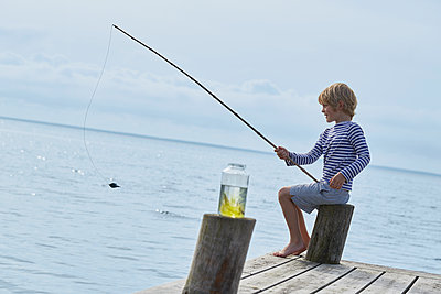 Boy fishing off lakeside dock - p1023m1172724 by Francis Pictures