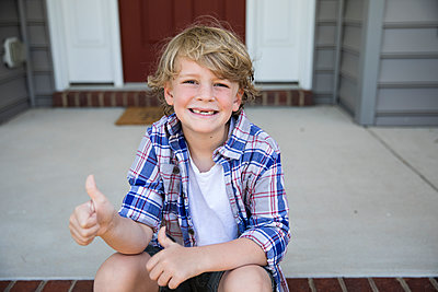 Toothless First Grade Boy Gives Thumbs Up While Sitting on Brick Steps - p1166m2212718 by Cavan Images