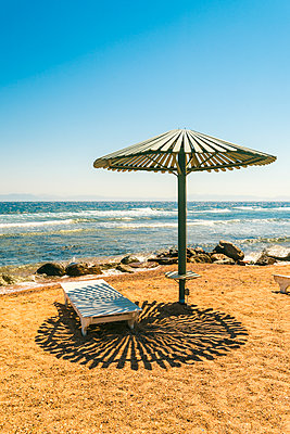 A wooden sunshade and a sunlounger on the beach  - p1332m1502621 by Tamboly