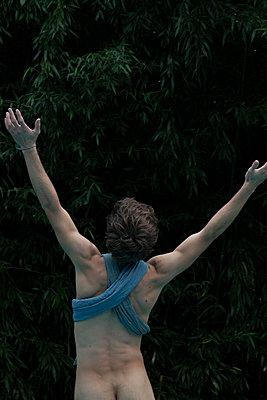 Nackter Mann streckt Arme in die Luft - p1650m2231577 von Hanna Sachau