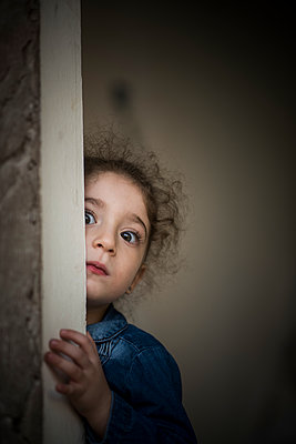 Scared little girl hiding  - p794m2031096 by Mohamad Itani