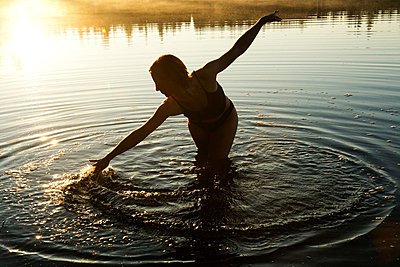 Woman touching water in lake - p924m734475f by Pete Saloutos
