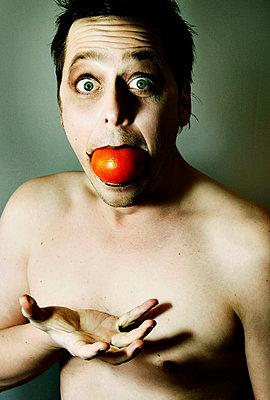 Mann mit Tomate im Mund - p979m1118733 von Sabrina Tauscher