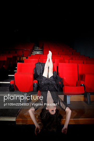 Young woman lying head first on a seat in the cinema hall - p1105m2254503 by Virginie Plauchut