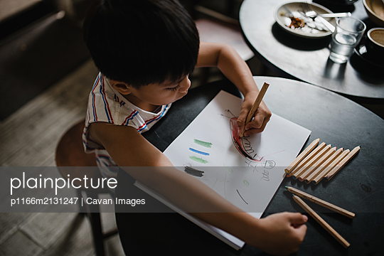 Boy drawing with colour pencils - p1166m2131247 by Cavan Images