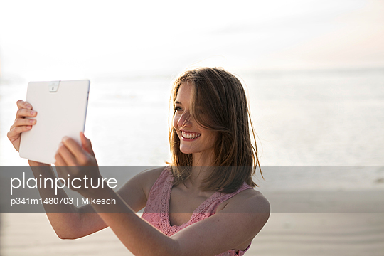 Young woman on beach using tablet computer - p341m1480703 by Mikesch