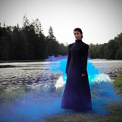Woman with black dress in a blue smoke - p1521m2215013 by Charlotte Zobel