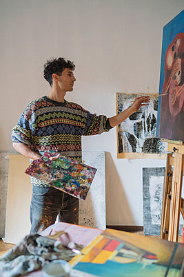 Male artist painting canvas in artists studio - p429m1547672 by Arno Images