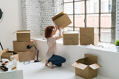 Mid adult woman moving into industrial style apartment, stacking boxes - p429m2091412 by Garage Island Crew