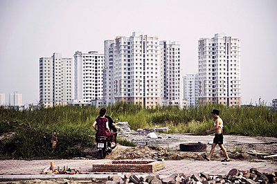 A motorbike drives off-road in a wasteland area surrounding Ciputra's towers, which rise up in the background, Hanoi, Vietnam, Southeast Asia - p934m832724 by Raphaël Olivier