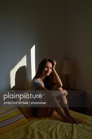 Smiling woman sit on bed in the bedroom - p1607m2181544 by zhushman