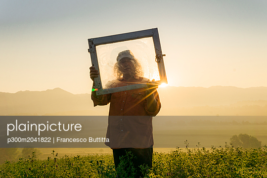 Italy, Tuscany, Borgo San Lorenzo, senior man holding window frame in field at sunrise above rural landscape - p300m2041822 von Francesco Buttitta