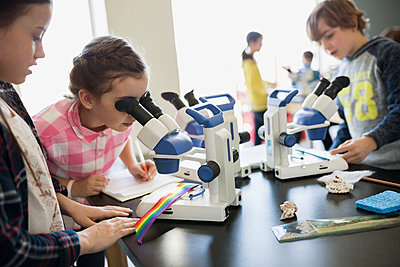 Students using microscopes in science laboratory classroom - p1192m1019861f by Hero Images