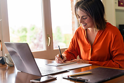 Smiling businesswoman writing in notepad while working at home - p300m2206517 by VITTA GALLERY