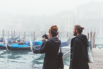 Couple photographing gondolas on misty canal, Venice, Italy - p429m1408105 by Eugenio Marongiu