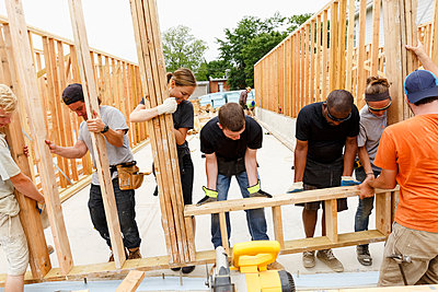 Volunteers lifting framed wall at construction site - p555m1522818 by Roberto Westbrook