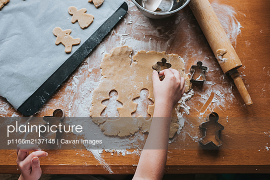 Young girl cutting our gingerbread man from dough using cutters - p1166m2137148 by Cavan Images