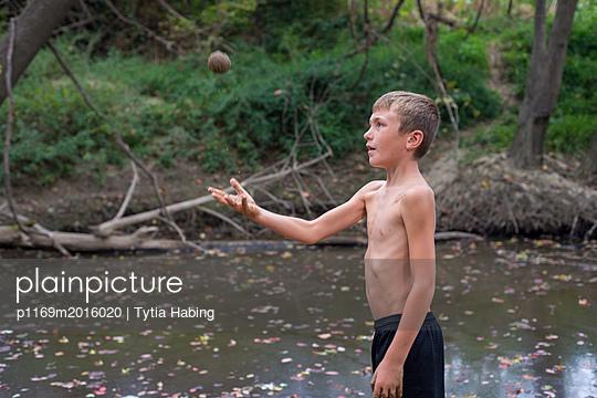 Junge wirft Sandkugel in die Luft - p1169m2016020 von Tytia Habing