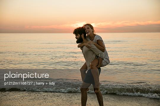 Junges Paar - Sonnenuntergang am Strand - p1212m1168727 von harry + lidy
