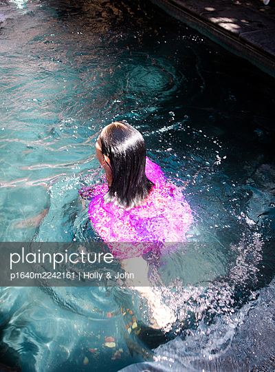 Woman in purple dress swims in the swimming pool - p1640m2242161 by Holly & John