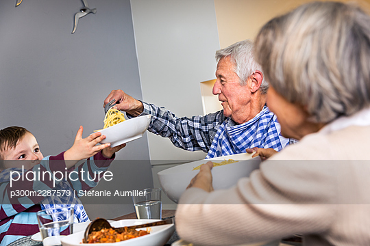 Multi-generation family having food together at home - p300m2287579 by Stefanie Aumiller