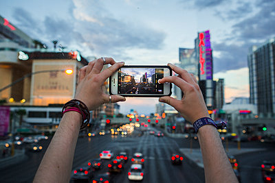 Woman takes a picture with smartphone at twilight - p1057m1466822 by Stephen Shepherd