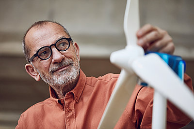 Senior engineer working on wind energy solutions, looking at wind turbine - p300m2171134 by Maya Claussen