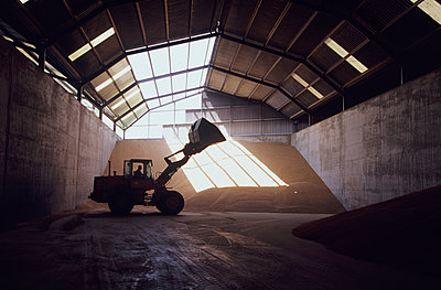 Front-end loader in grain warehouse - p555m1419198 by Chris Sattlberger