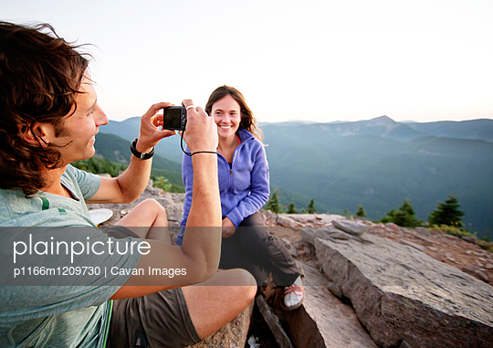 Woman looking at boyfriend photographing while sitting on mountain - p1166m1209730 by Cavan Images